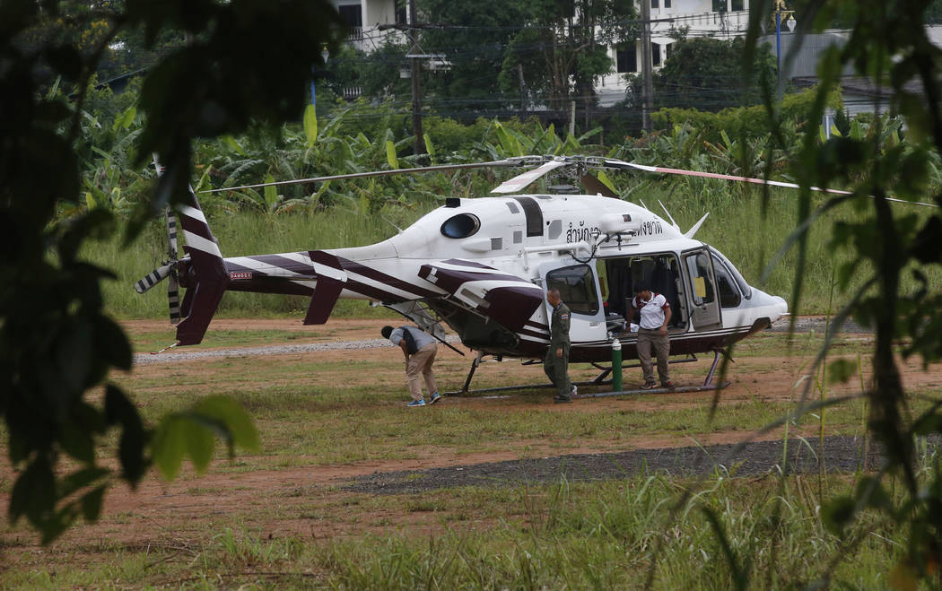 A helicopter waits near the cave for more evacuations of the boys and their soccer coach who have been trapped since June 23, in Mae Sai, Chiang Rai province, northern Thailand Monday, July 9, 201 ...