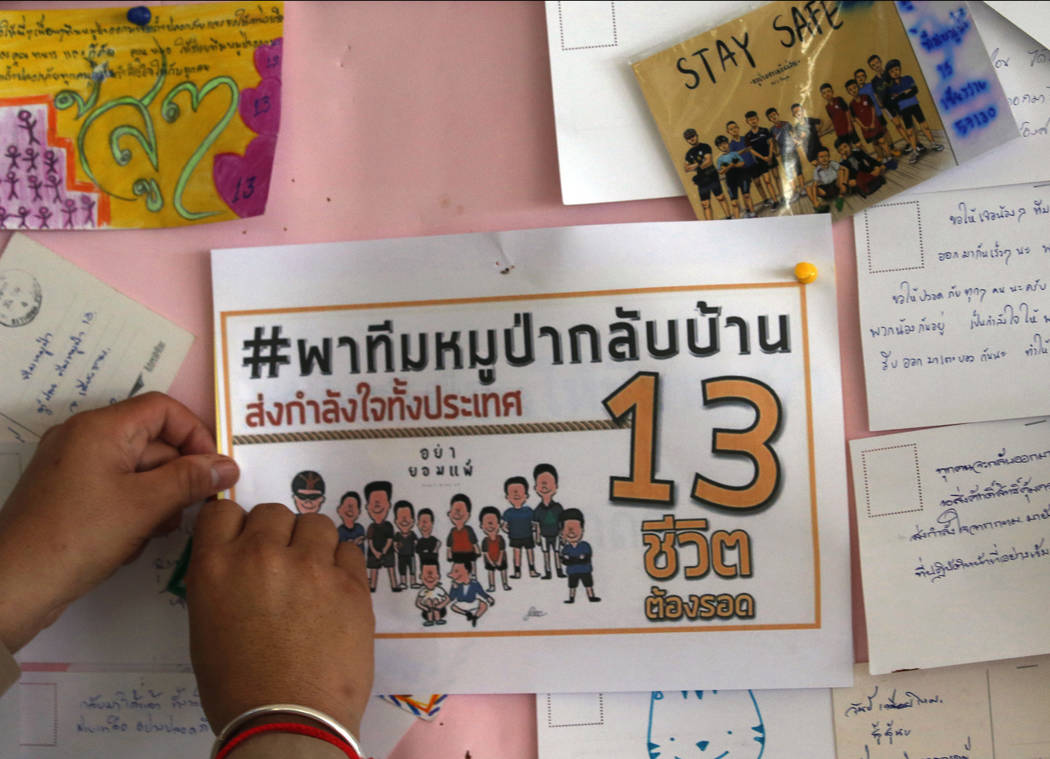 A Thai well wisher put poster to pray for boys and their soccer coach who have been trapped since June 23, in Mae Sai, Chiang Rai province, northern Thailand Monday, July 9, 2018. Expert divers Su ...