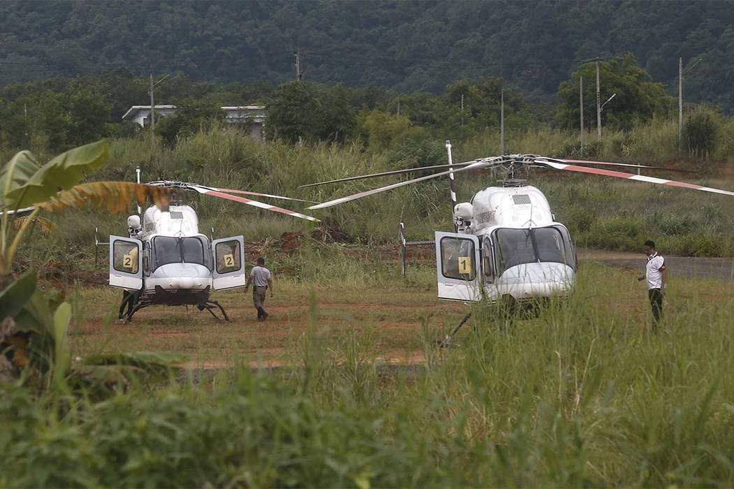 Two helicopters wait near the cave for more evacuations of the boys and their soccer coach who have been trapped since June 23, in Mae Sai, Chiang Rai province, northern Thailand Monday, July 9, 2 ...