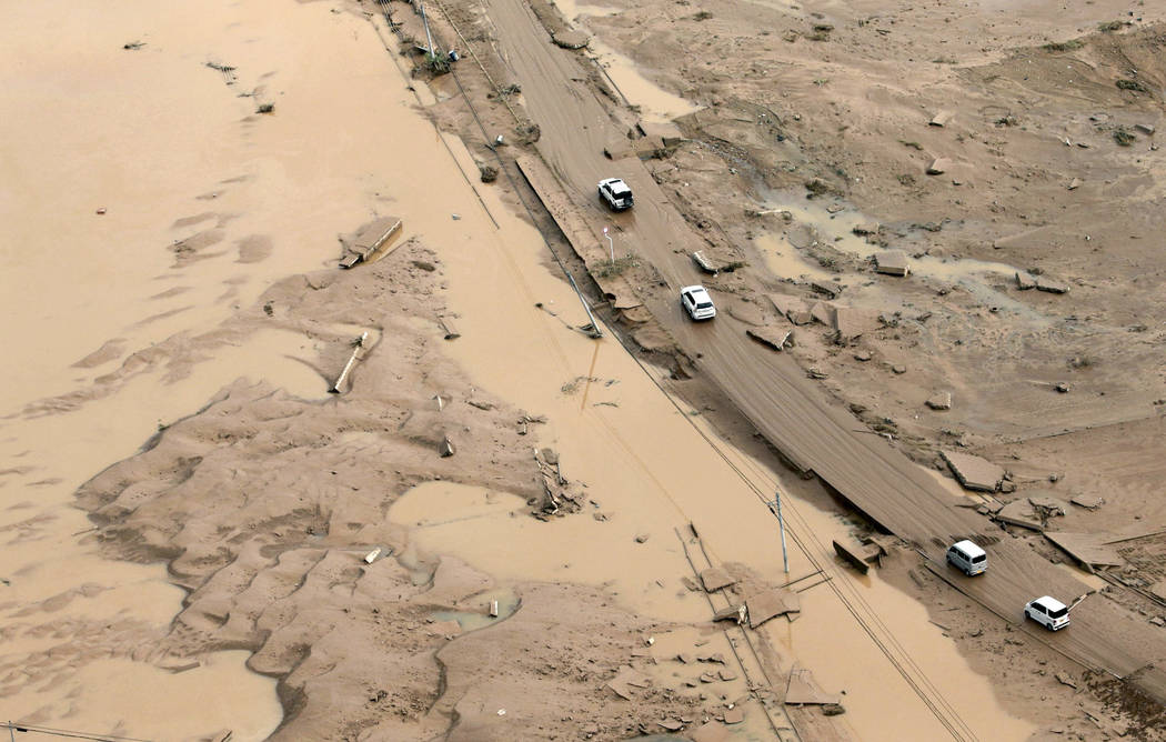 Vehicles make their way through a mud-covered road in Kurashiki, Okayama prefecture, western Japan Monday, July 9, 2018. People prepared for risky search and cleanup efforts in southwestern Japan ...