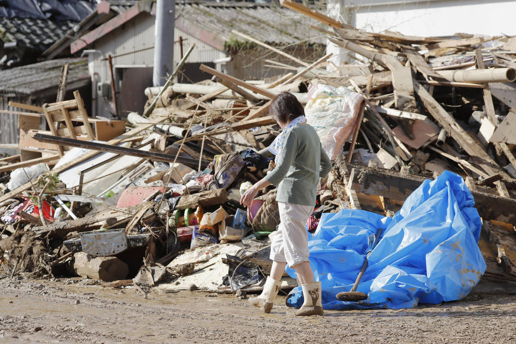 A woman walks past debris caused by a heavy rain in Uwajima, Ehime prefecture, western Japan Monday, July 9, 2018. People prepared for risky search and cleanup efforts in southwestern Japan on Mon ...