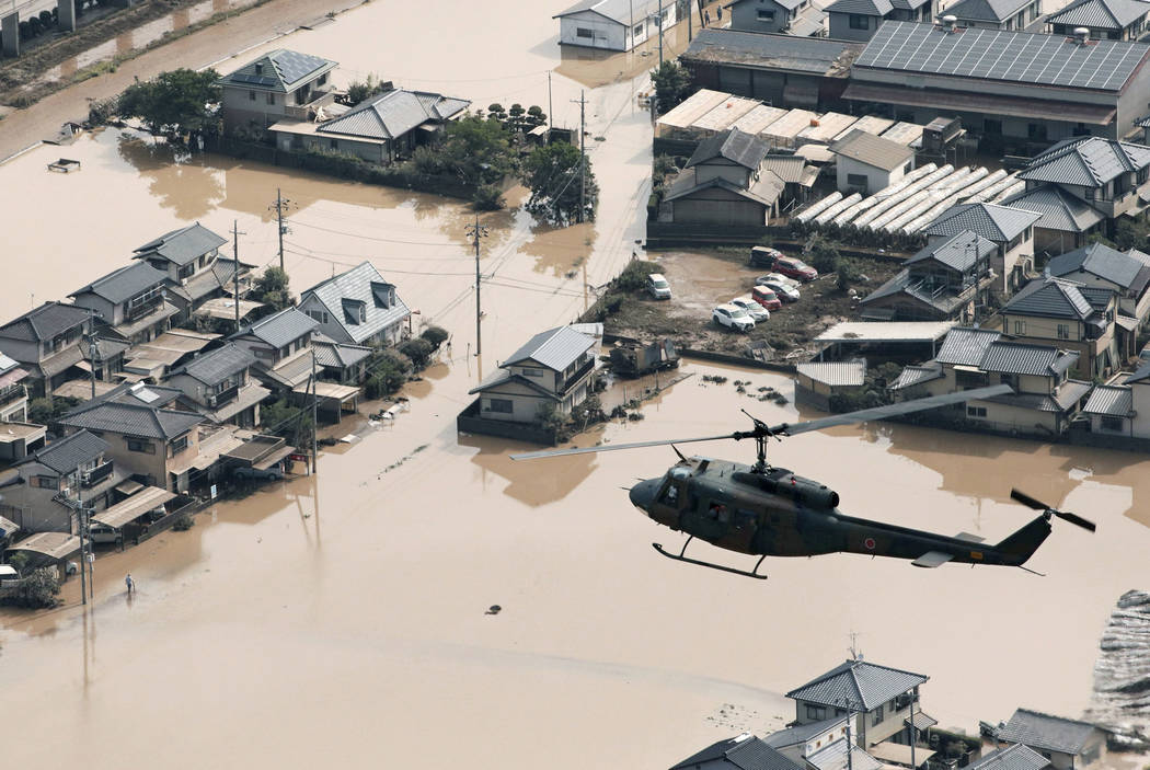 A helicopter flies over a flooded housing area in Kurashiki, Okayama prefecture, western Japan Monday, July 9, 2018. People prepared for risky search and cleanup efforts in southwestern Japan on M ...