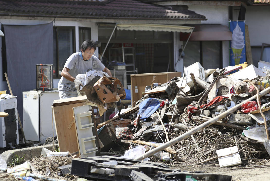 A man cleans debris caused by a heavy rain in Soja, Okayama prefecture, western Japan Monday, July 9, 2018. People prepared for risky search and cleanup efforts in southwestern Japan on Monday, w ...