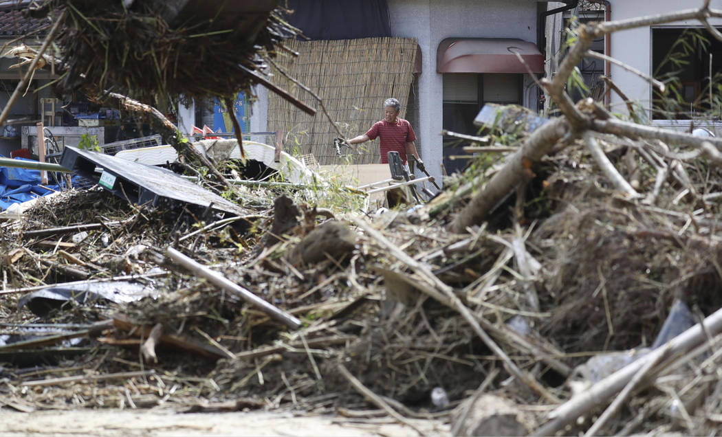 A man cleans debris caused by a heavy rain in Soja, Okayama prefecture, western Japan Monday, July 9, 2018. People prepared for risky search and cleanup efforts in southwestern Japan on Monday, wh ...