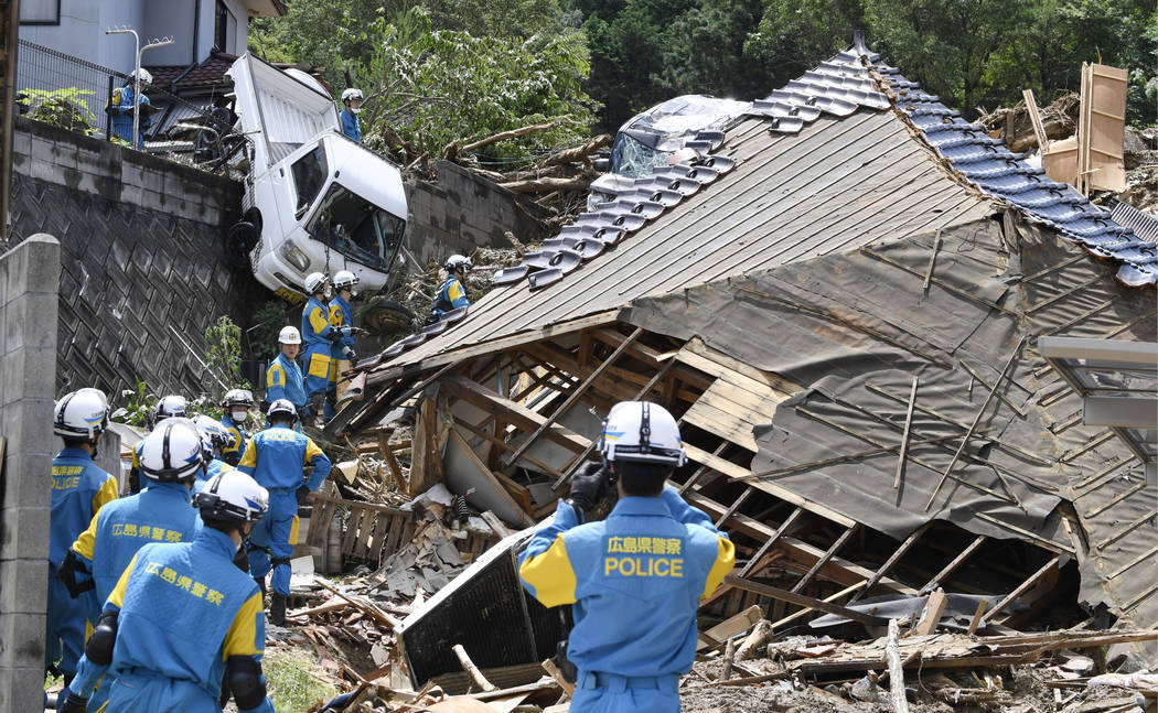 Rescuers prepare to start a search mission for missing person at the site of a landslide in Kumano town, Hiroshima prefecture, western Japan Monday, July 9, 2018. People prepared for risky search ...