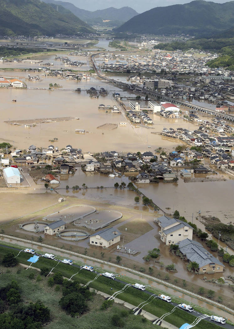 Operations to discharge water are underway at an submerged housing area in Kurashiki, Okayama prefecture, western Japan Monday, July 9, 2018. People prepared for risky search and cleanup efforts i ...