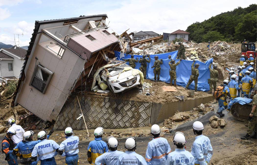 Rescuers conduct a search operation for missing persons in Kumano town, Hiroshima prefecture, western Japan Monday, July 9, 2018. People prepared for risky search and cleanup efforts in southweste ...