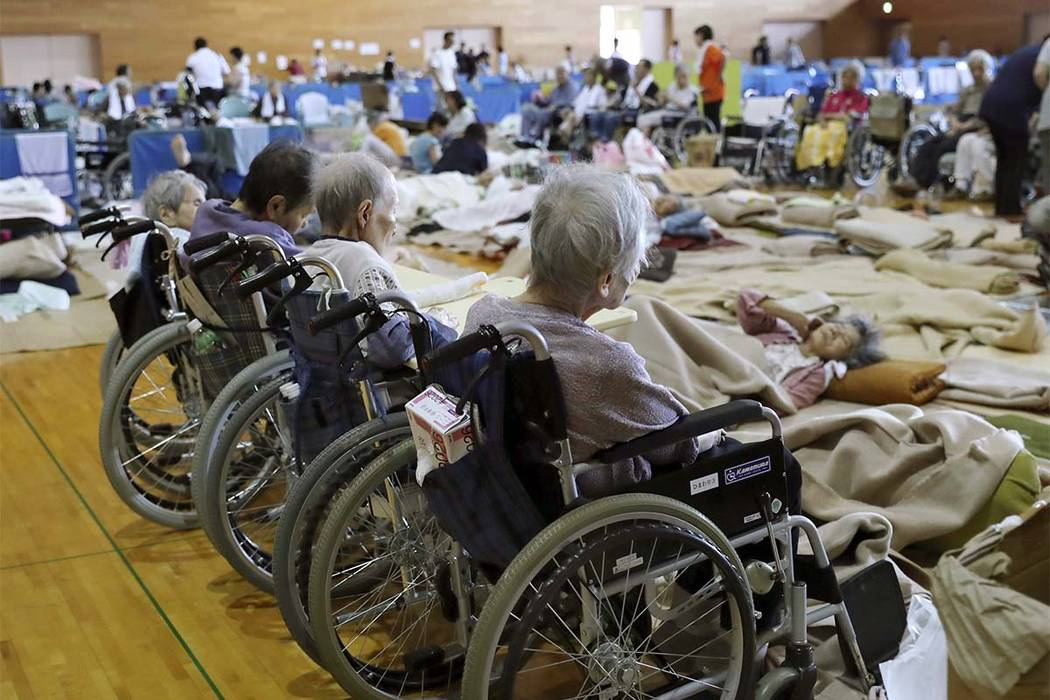 Elderly people from a nursing home take shelter following a heavy rain, in Soja, Okayama prefecture, western Japan Monday, July 9, 2018. People prepared for risky search and cleanup efforts in sou ...