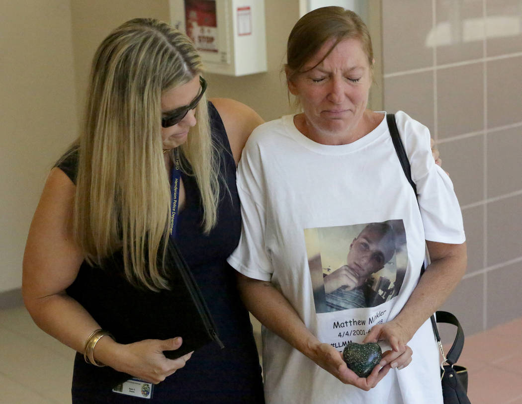 Jamie Shanklin is comforted by Sara Owen, victim advocate for the Metropolitan Police Department, as she clutches a small heart-shaped stone that contains the ashes of her son, Matthew Minkler, af ...