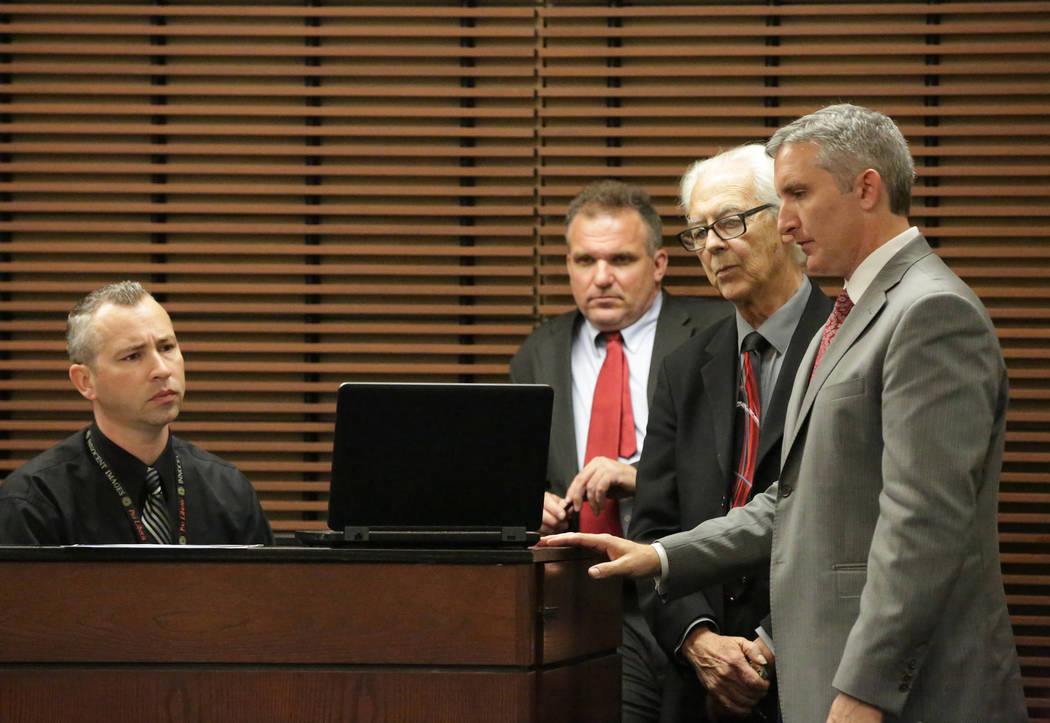 Henderson police Detective Wayne Nichols, seated, and defense attorneys Keith Brower and Bill Terry watch as prosecutor Giancarlo Pesci, right, plays a video, made just after the shooting death of ...
