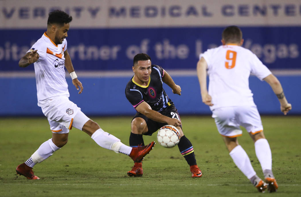 Las Vegas Lights FC midfielder Julian Portugal (26) loses possession of the ball to Tulsa Roughnecks FC forward Jhon Pirez, left, and Tulsa Roughnecks FC midfielder Michael Gamble (9) during the s ...