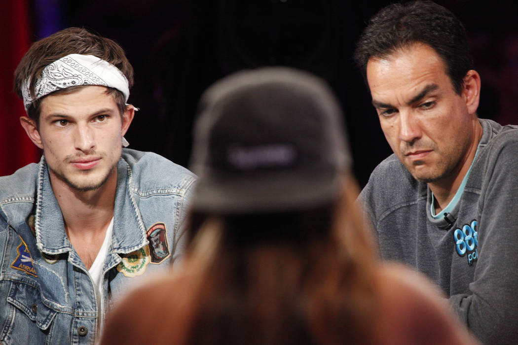 Mario Mosbock, left, and Ahmid Amin watch Kelly Minkin (center) during day five of the World Series of Poker tournament at the ESPN feature table at the Rio Convention Center in Las Vegas, Monday, ...