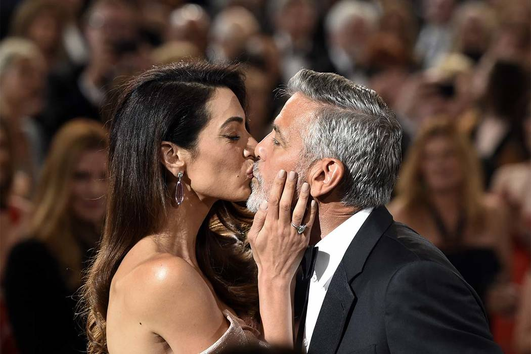 In this June 7, 2018 file photo, actor/director George Clooney gets a kiss from his wife Amal as he arrives for the 46th AFI Life Achievement Award in Los Angeles. (Chris Pizzello/Invision/AP, FIle)