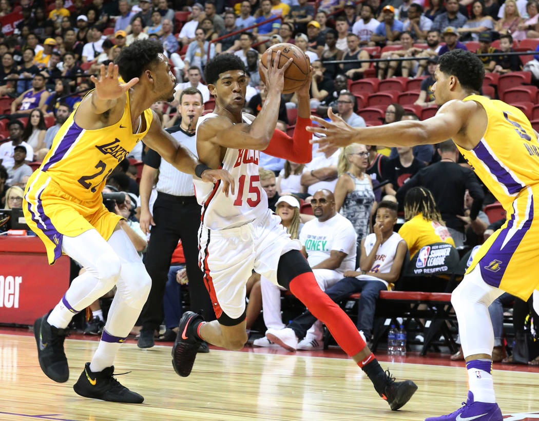 The Los Angeles Lakers guard Josh Hart, right, and forward Jonathan Williams (21) try to defend the Chicago Bulls guard Chandler Hutchinson (15) during an NBA Summer League basketball game at the ...