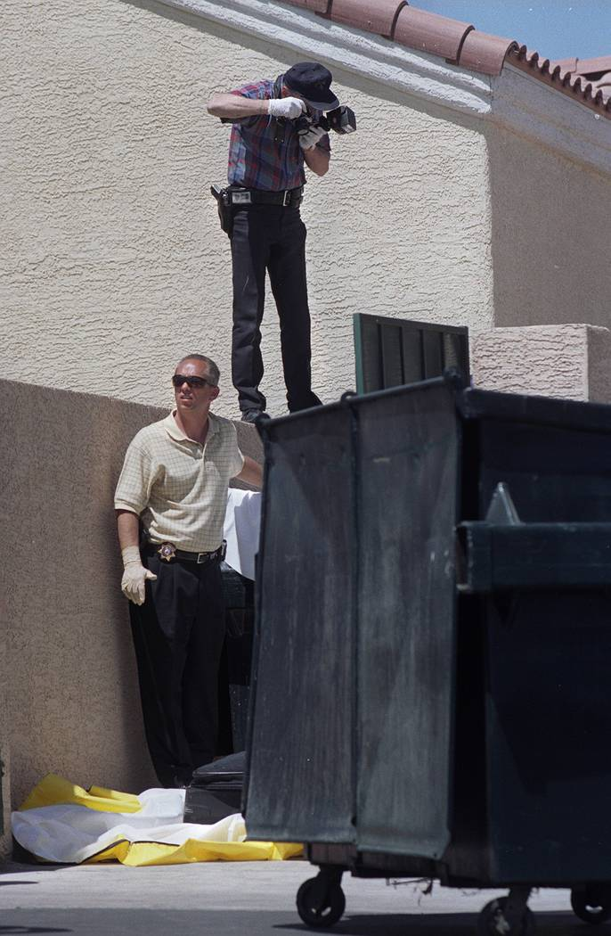 Homicide investigators photograph a large black suitcase containing a body at the Copper Sands apartment complex on April 24, 2002.  RJ Photo by Steve Andrascik