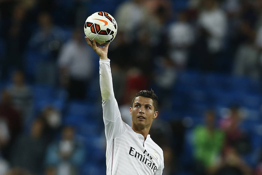 In this Sept. 23, 2014 file photo Real's Cristiano Ronaldo holds the ball as he celebrates his four goals during a Spanish La Liga soccer match between Real Madrid and Elche at the Santiago Bernab ...