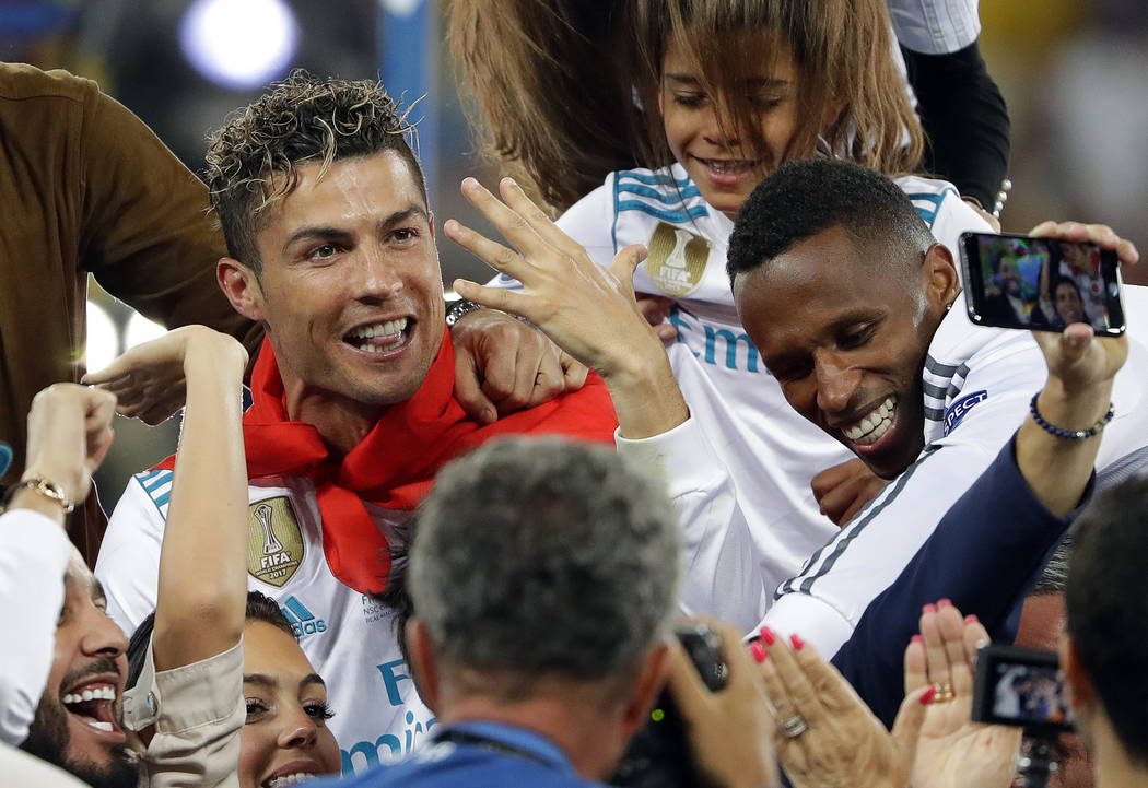 In this Saturday, May 26, 2018 file photo Real Madrid's Cristiano Ronaldo celebrates with fans after winning the Champions League Final soccer match between Real Madrid and Liverpool at the Olimpi ...
