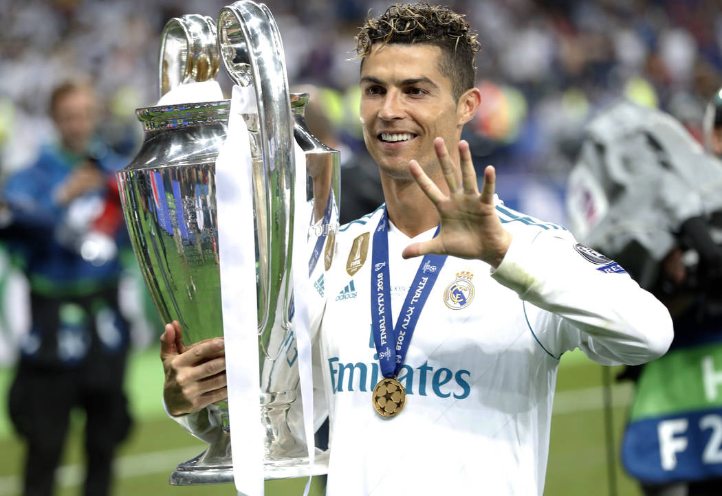 In this Saturday, May 26, 2018 file photo Real Madrid's Cristiano Ronaldo celebrates with the trophy after winning the Champions League Final soccer match between Real Madrid and Liverpool at the ...