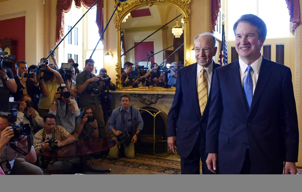 Supreme Court nominee Brett Kavanaugh, right, and Sen. Chuck Grassley, R-Iowa, second from right, walk past the press following a photo opportunity on Capitol Hill in Washington, Tuesday, July 10, ...