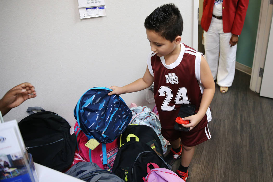 Vince, 7, whose mother declined to give a last name, receives a backpack during a free back to school immunization and health clinic event hosted at the FirstMed Health and Wellness Center in Las ...