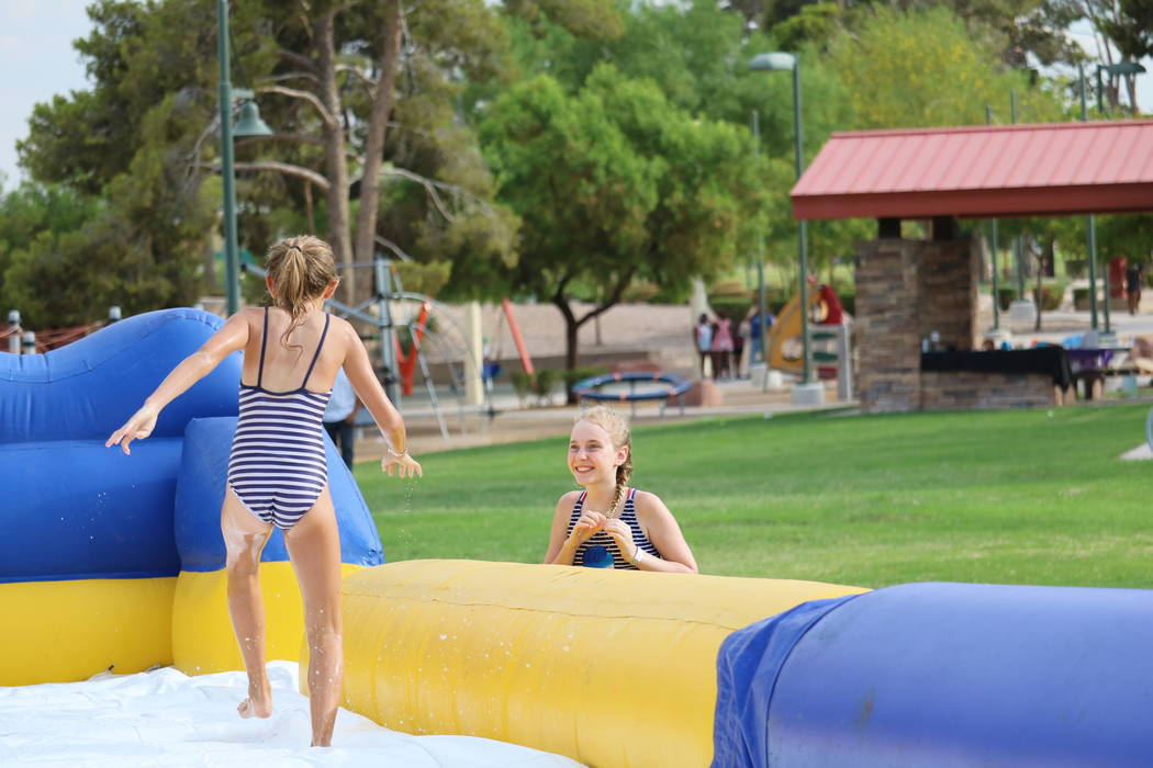 Willow Mason, 12, right, greets friend Savannah Winblad, 11, left, as she runs off the Freestyle Hippo water slide at the inaugural Slides, Rides & Rock and Roll event at Craig Ranch Regional ...