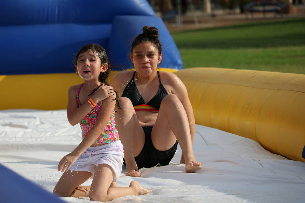 Emma Rodriguez, 6, left and Gabby Tallarzo, 12, right, react after descending the Freestyle Hippo water slide at the inaugural Slides, Rides & Rock and Roll event at Craig Ranch Regional Park ...