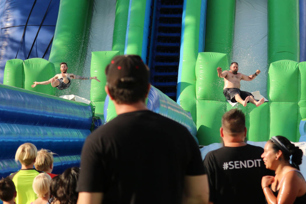 Onlookers watch as two men come flying off the 51' Skyscraper water slide at the inaugural Slides, Rides & Rock and Roll event at Craig Ranch Regional Park in North Las Vegas, Saturday, July 1 ...