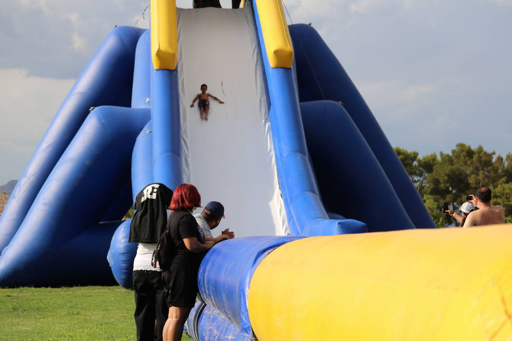 Onlookers watch as Talen Ginanni, 9, of Las Vegas, slides down the Freestyle Hippo water slide at the inaugural Slides, Rides & Rock and Roll event at Craig Ranch Regional Park in North Las Ve ...