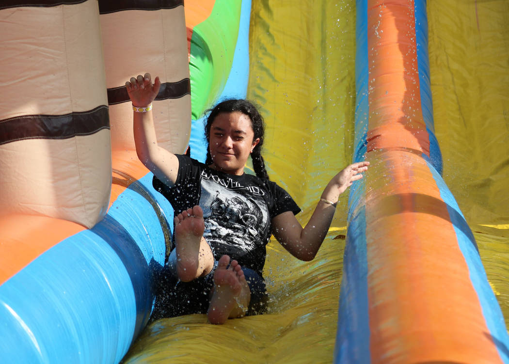 KK Samana, 14, takes a break from ride operator duty to cool off on a water slide at the inaugural Slides, Rides & Rock and Roll event at Craig Ranch Regional Park in North Las Vegas, Saturday ...