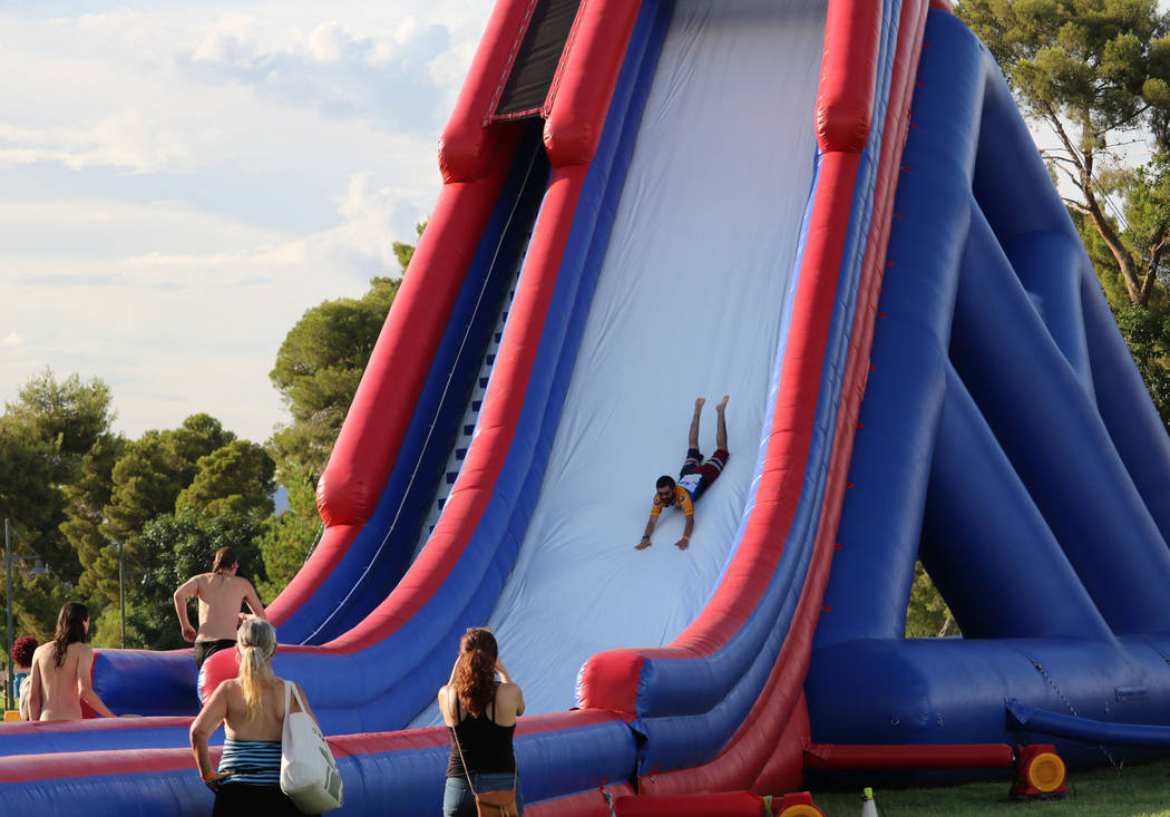 Onlookers watch a brave soul descend a water slide face first at the inaugural Slides, Rides & Rock and Roll event at Craig Ranch Regional Park in North Las Vegas, Saturday, July 14, 2018. Hun ...