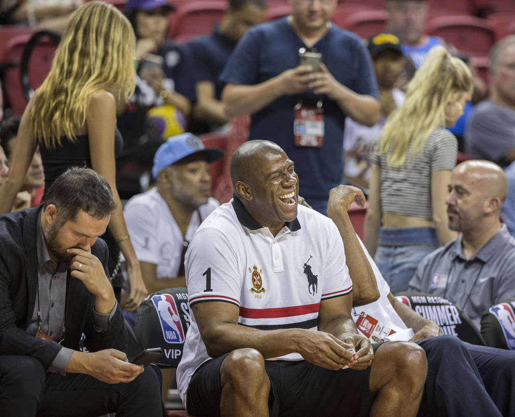 Former Lakers player and current general manager Magic Johnson shares a laugh with friends during Los Angeles' NBA Summer League game with the New York Knicks on Tuesday, July 10, 2018, at the Tho ...