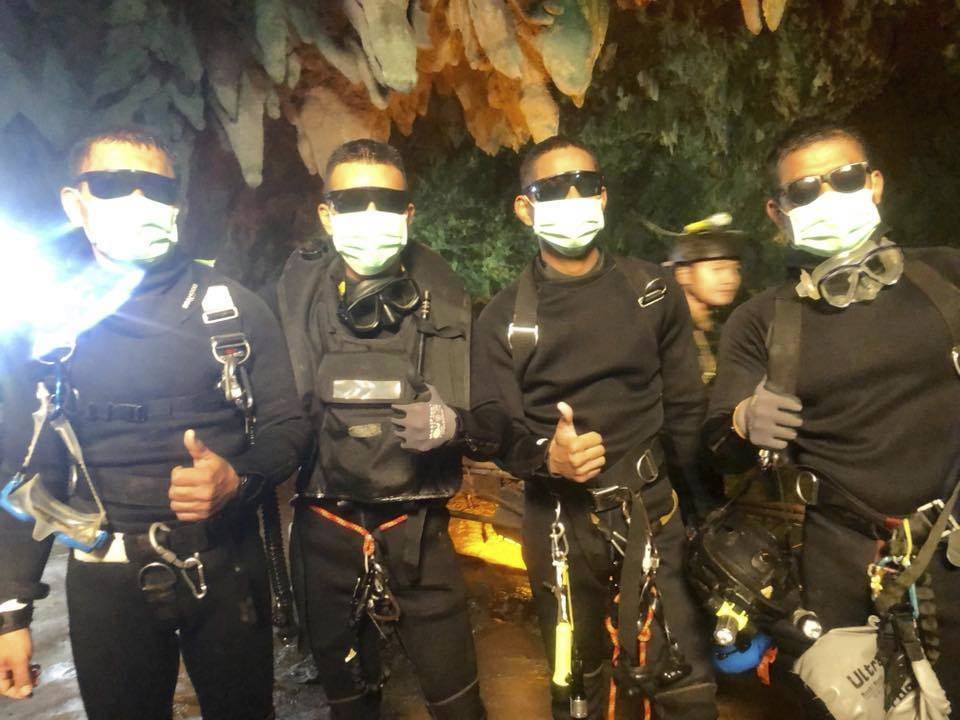 In this undated photo released by Royal Thai Navy on Tuesday, July 10, 2018 show the last four Thai Navy SEALs come out safely after completing the rescued mission inside a cave where 12 boys and ...