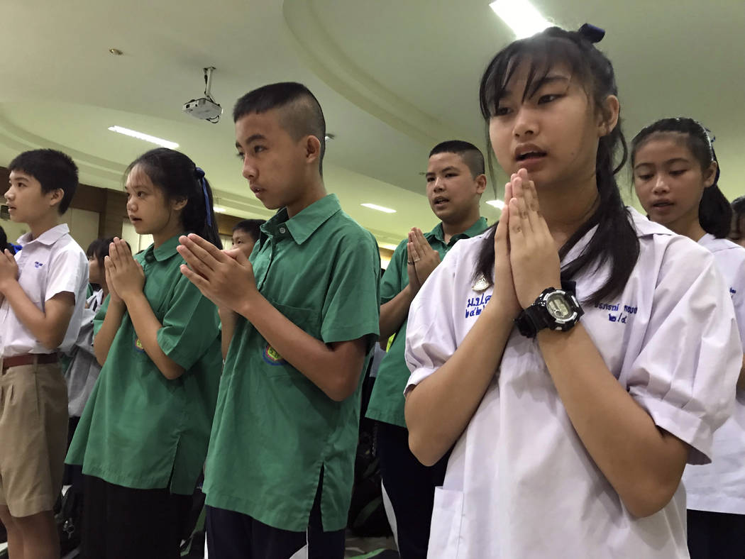 Students pray at Maesaiprasitsart school where six out of the rescued 12 boys study as they cheer the successful rescue in the Mae Sai district in Chiang Rai province, northern Thailand, Wednesday ...
