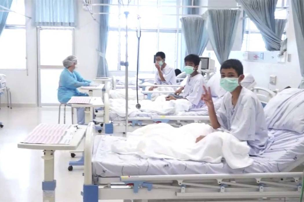 In this image made from video, released by the Thailand Government Spokesman Bureau, three of the 12 boys are seen recovering in their hospital beds after being rescued along with their coach from ...