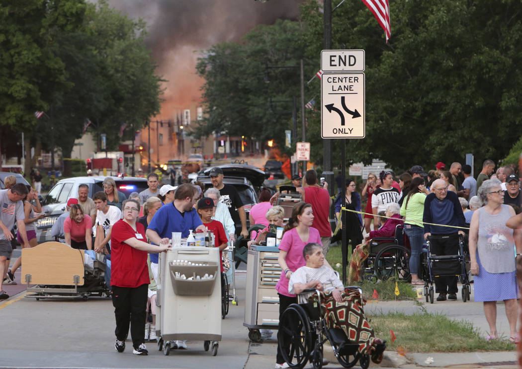 People evacuate as they were told to move farther away the scene of an explosion in downtown Sun Prairie, Wis., Tuesday, July 10, 2018. The explosion rocked the downtown area of Sun Prairie, a sub ...
