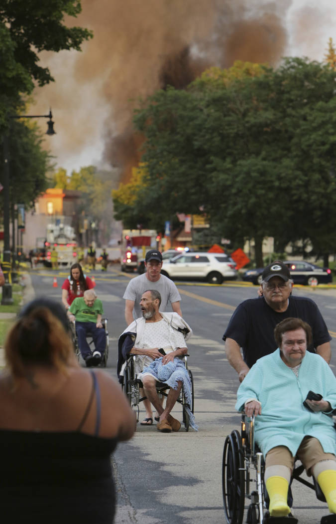 Residents are relocated from a nearby home after an explosion in downtown Sun Prairie, Wis., Tuesday, July 10, 2018. The explosion rocked the downtown area of Sun Prairie, a suburb of Madison, aft ...