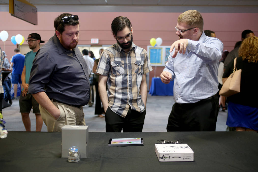 David Clark, left, and Roger Cruz listen to Joerg Radler, an engineer from Apple, at the College of Southern Nevada in Las Vegas, Thursday, July 12, 2018. Radler explained how students will be abl ...