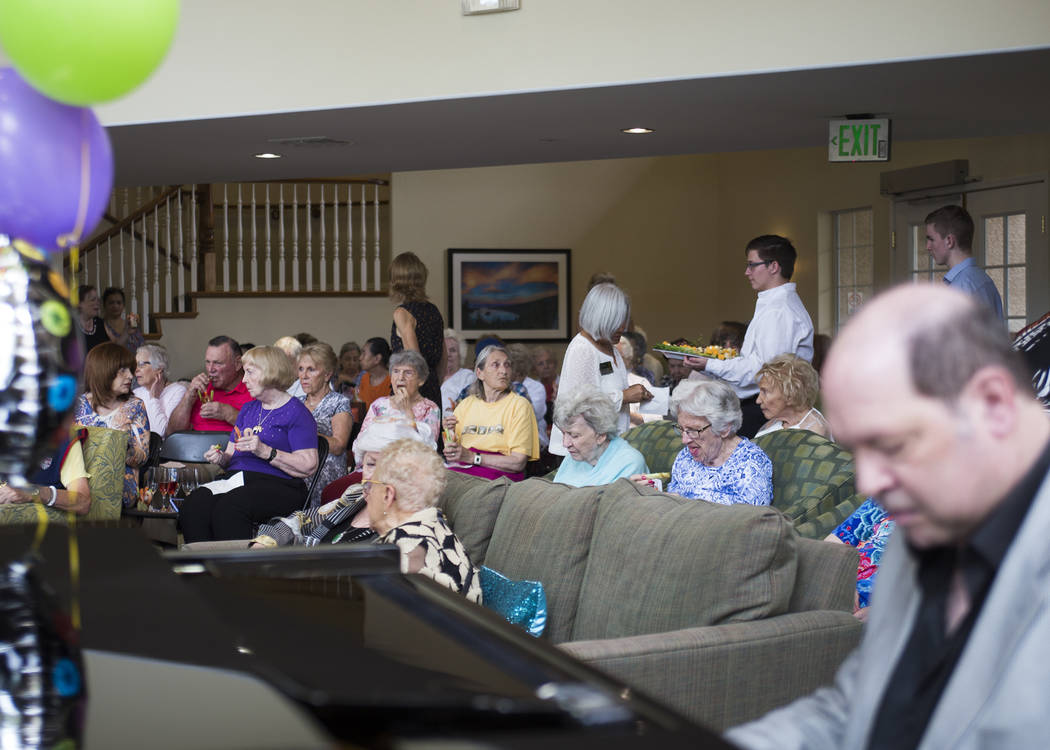 Sue Phelps hands Gene Stephens a Veterans Reporter News paper at his 100th birthday party at Atria Seville Senior Living in Las Vegas, Thursday, July 12, 2018. Dozens of family and friends attende ...