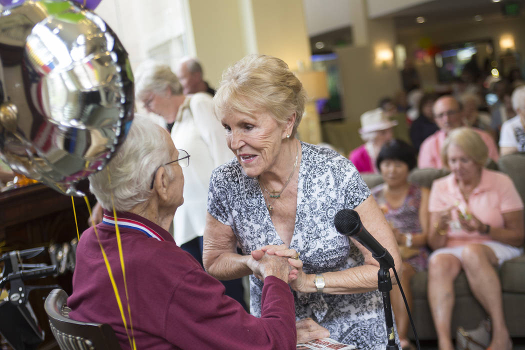 Elle Wilcox greets Gene Stephens at his 100th birthday party at Atria Seville Senior Living in Las Vegas, Thursday, July 12, 2018. Dozens of family and friends attended to celebrate with him. Wilc ...
