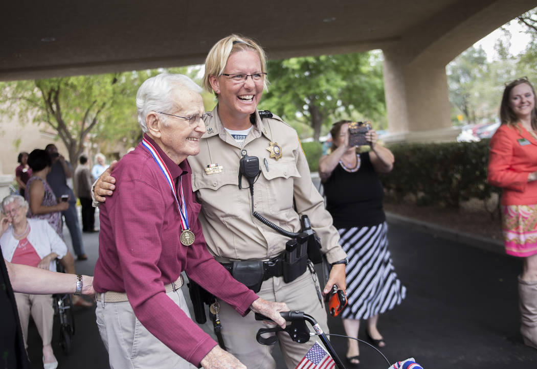 Officer Kelly Cannon hugs Gene Stephens at his 100th birthday party at Atria Seville Senior Living in Las Vegas, Thursday, July 12, 2018. Dozens of motorcyclists stopped by as well as a bagpiper f ...