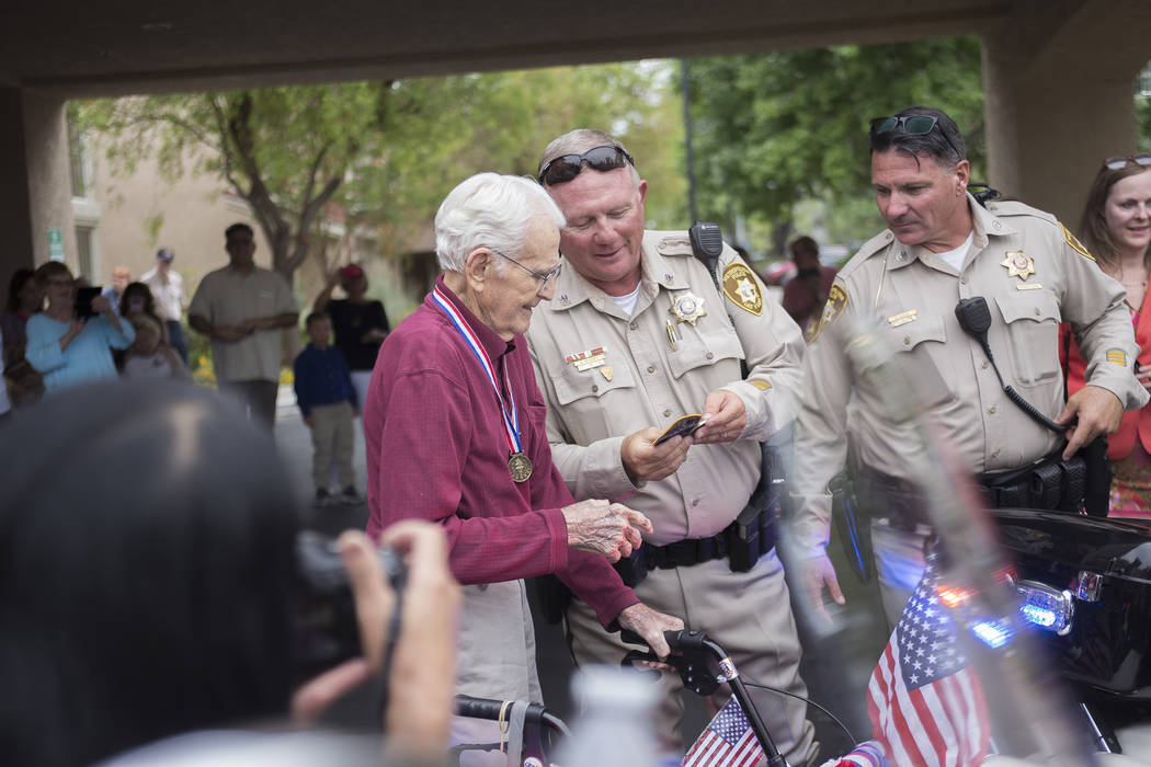 Officer Stephen Ritchey, left, and Officer Michael Lemley give Gene Stephens an Oct. 1 patch and Oct. 1 challenge coin as gifts at his 100th birthday party at Atria Seville Senior Living in Las Ve ...