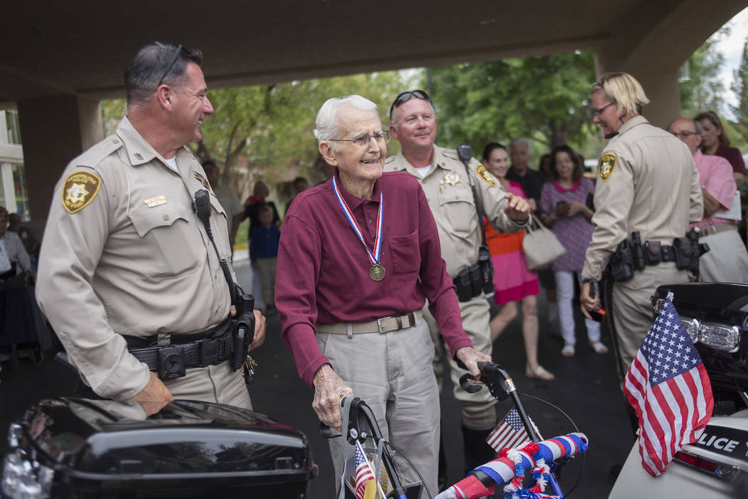 Officer Michael Lemley, left, and Gene Stephens at his 100th birthday party at Atria Seville Senior Living in Las Vegas, Thursday, July 12, 2018. Dozens of motorcyclists stopped by as well as a ba ...