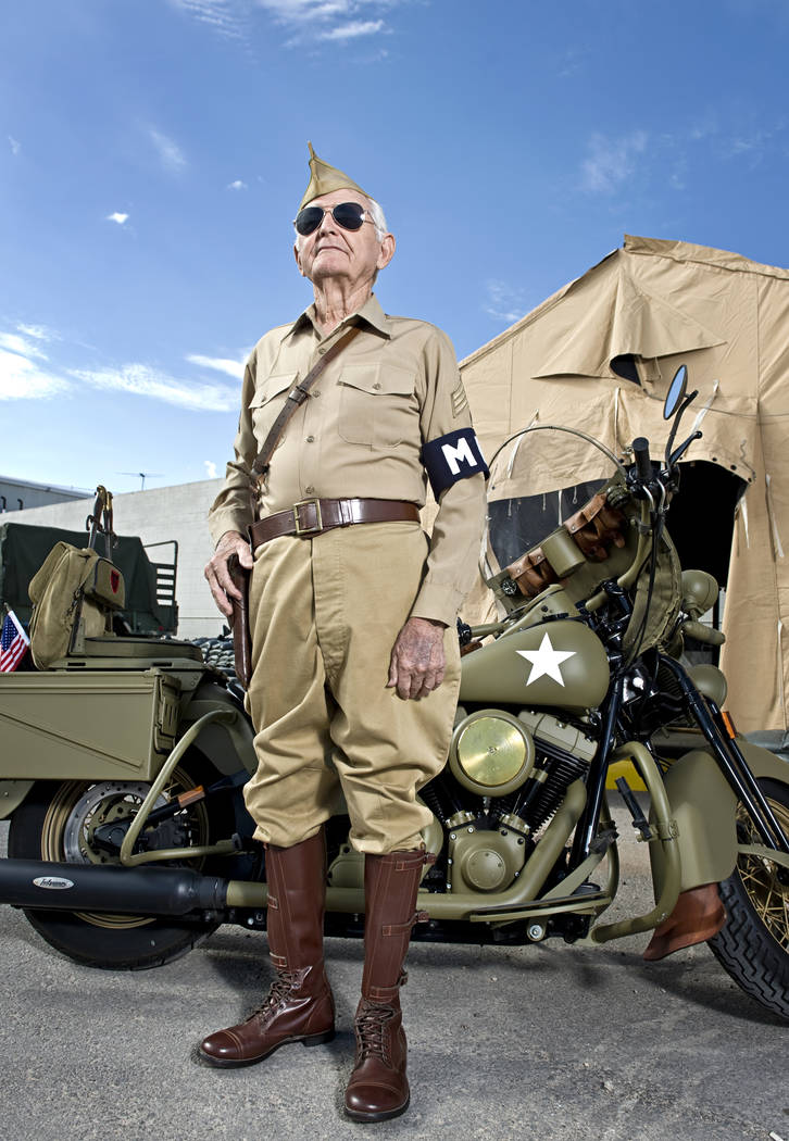 World War II veteran Gene Stephens, then 94, wears his Military Police Corps uniform as he poses next to a vintage motorcycle at Battlefield Vegas, a military theme park on Industrial Road near Ci ...