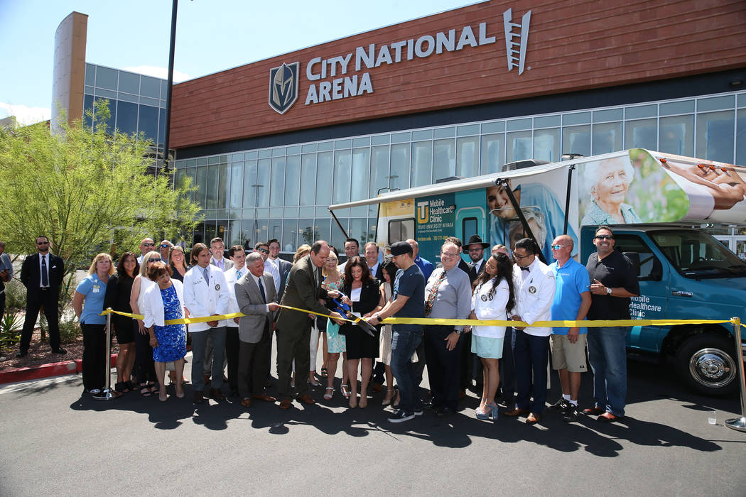 People participate in the ribbon cutting ceremony for the new Touro University Nevada mobile healthcare clinic parked outside at City National Arena in Las Vegas, Thursday, July 19, 2018. Erik Ver ...