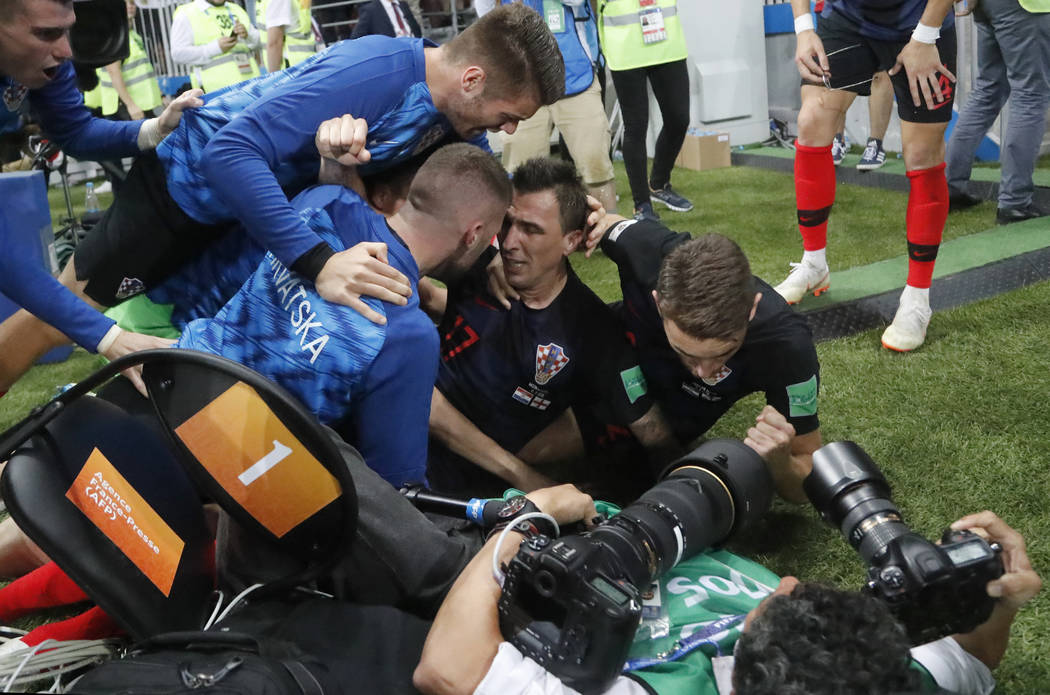 Croatia's Mario Mandzukic, sits on the ground after he fell over a photographer when celebrating his side's second goal during the semifinal match between Croatia and England at the 2018 soccer Wo ...