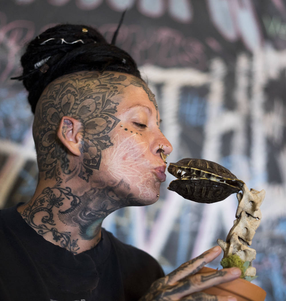 "Erin Emre, curator and founder of The Dark Arts Market, kisses ""The Audrey"" at Cornish Pasty Co. in Las Vegas, Tuesday, July 10, 2018. According to Emre, the art piece is made out of dee ..."