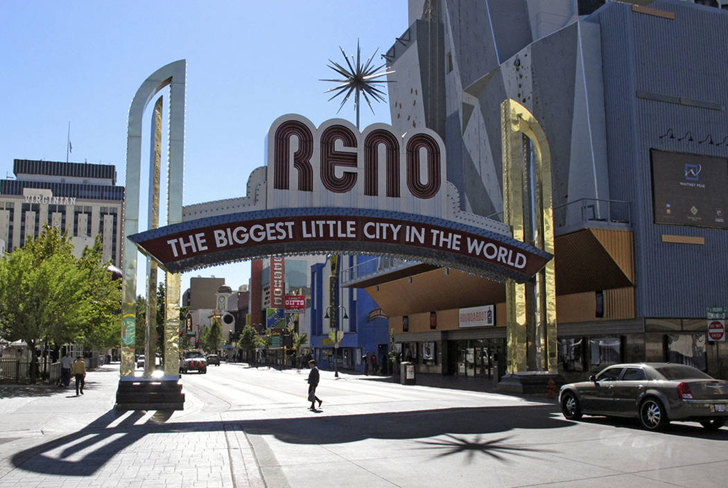A pedestrian makes their way beneath the famous Reno arch as traffic passes on Virginia Street in downtown Reno. (Scott Sonner/The Associated Press)