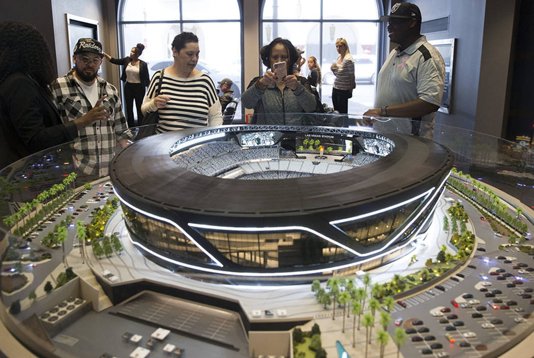 Kaipo Dean, from left, his sister Chianti Lloyd, mother Roxy Dean, and brother-in-law, Dewan Lloyd, view a Raiders stadium model on display at the Las Vegas stadium preview center at Town Square, ...