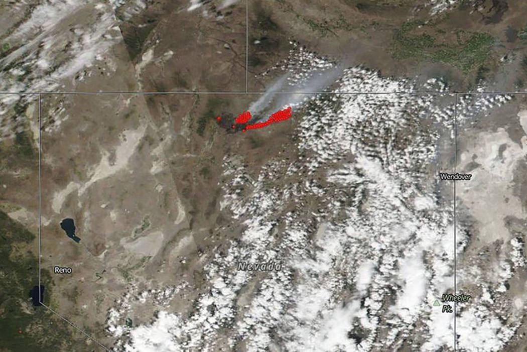 This July 8, 2018 satellite image from NASA's Suomi NPP satellite shows a wildfire, shown in red, also known as the Martin Fire, in Nevada, and smoke reaching to Idaho. (NASA via AP)