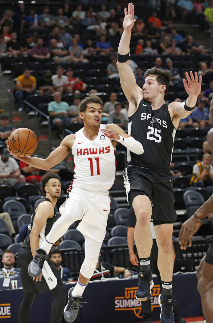 Atlanta Hawks guard Trae Young (11) passes the ball as San Antonio Spurs center Drew Eubanks (25) defends during the first half of an NBA summer league basketball game Tuesday, July 3, 2018, in Sa ...